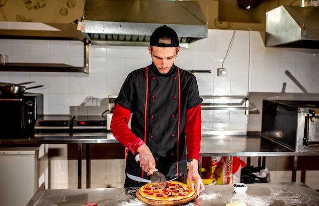 O chef corta a pizza com uma faca para servir