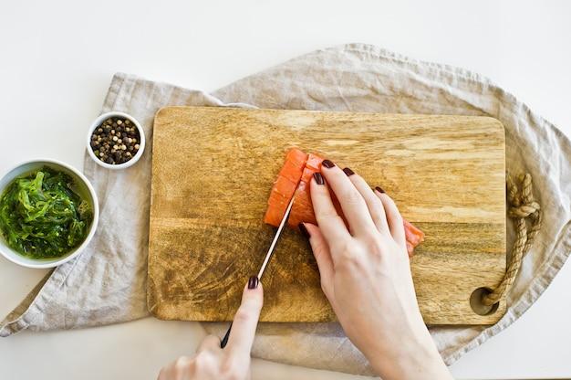 O chef corta filetes de salmão em uma tábua de madeira.