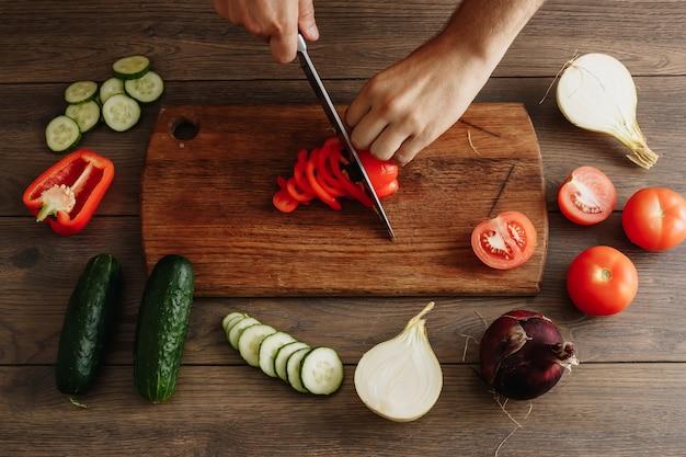 O chef corta legumes frescos e saborosos para cozinhar