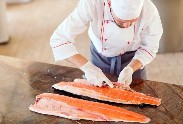 O chef corta o salmão em cima da mesa
