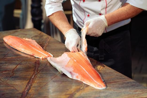O chef corta o salmão em cima da mesa.