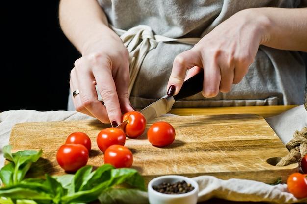 O chef corta tomate cereja em uma tábua de madeira.