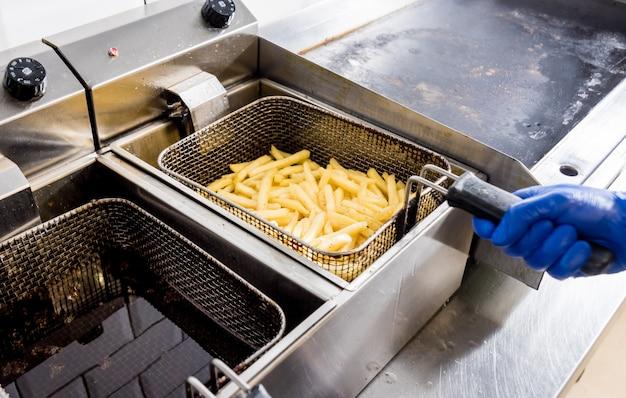 O chef cozinhar batatas fritas. restaurante.