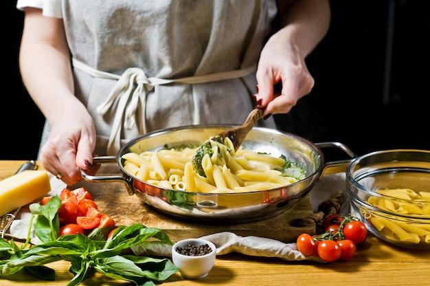 O chef cozinhar macarrão penne com espinafre.