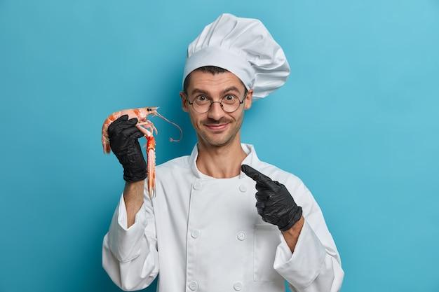 O chef cozinheiro positivo aponta para lagosta cozida, usa luvas pretas de borracha, uniforme branco