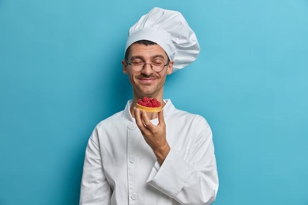 O chef da padaria sente o cheiro de bolos recém-assados feitos à mão, decorados com framboesa, trabalha na confeitaria, fecha os olhos de prazer