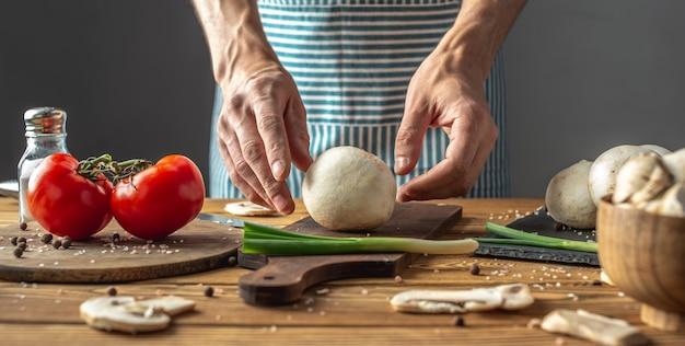O chef de avental azul pegou um cogumelo e vai preparar um delicioso prato de legumes e cogumelos.