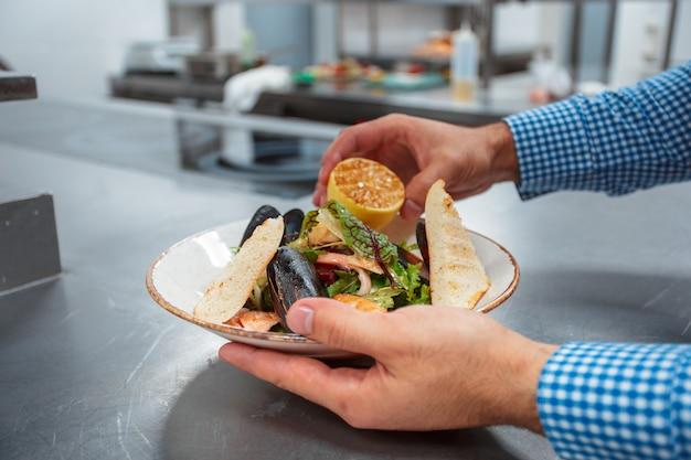 O chef de avental marrom, cozinhando em uma cozinha de restaurante
