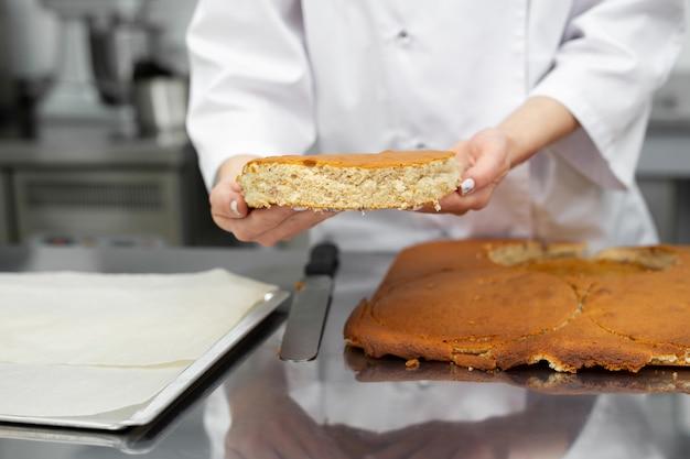 O chef de confeitaria corta um bolo de bolo de um biscoito.