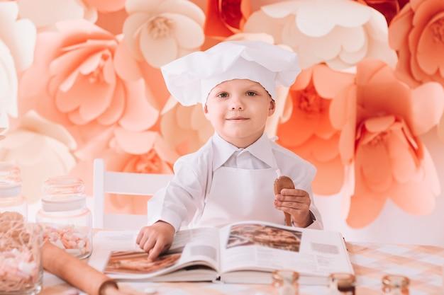 O chef de menino feliz escolhe uma receita culinária. o conceito de um hobby