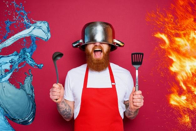 O chef do homem está pronto para lutar na superfície de cor de vinho da cozinha