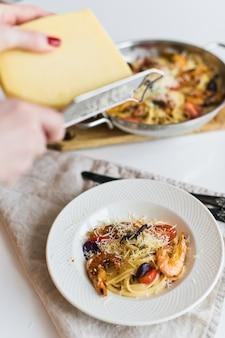 O chef esfrega macarrão parmesão com camarão.