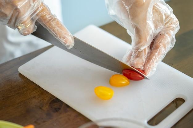 O chef está cortando vários tomates cereja coloridos.