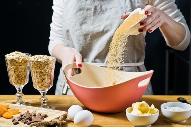 O chef está preparando biscoitos, despeja o açúcar mascavo em uma tigela.