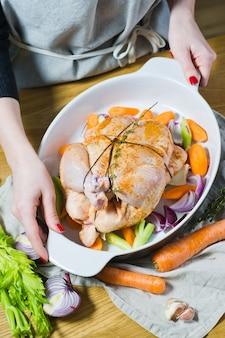 O chef está segurando uma panela com frango marinado inteiro.