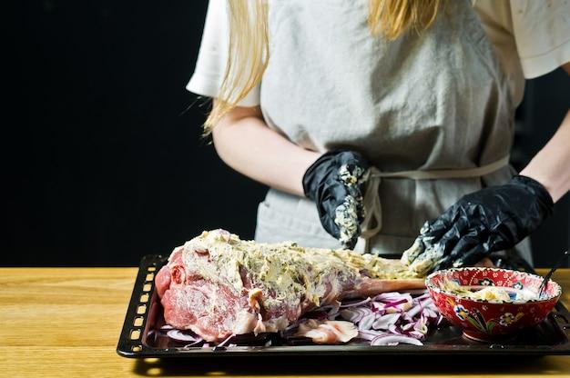 O chef marinata a perna de cabra crua.