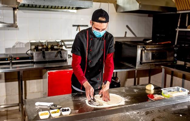 O chef ou fabricante de pizzas, com uma máscara médica contra o coronavírus, faz a massa de pizza em branco. conceito de fazer massa de pizza