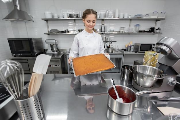 O chef pasteleiro tira do forno um pão-de-ló pronto para o bolo.