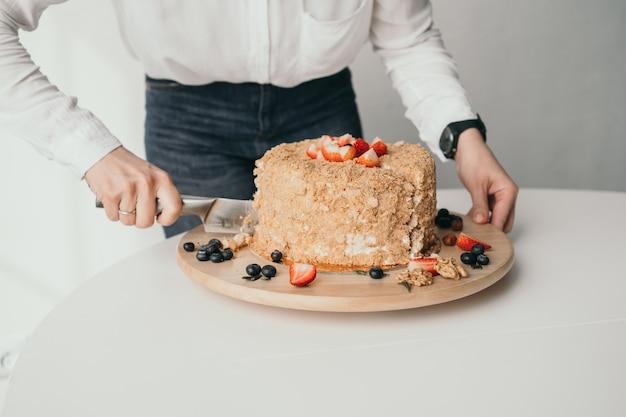 O chef pâtissier está cortando o bolo um delicioso bolo de mel é cortado com uma faca close do bolo de mel