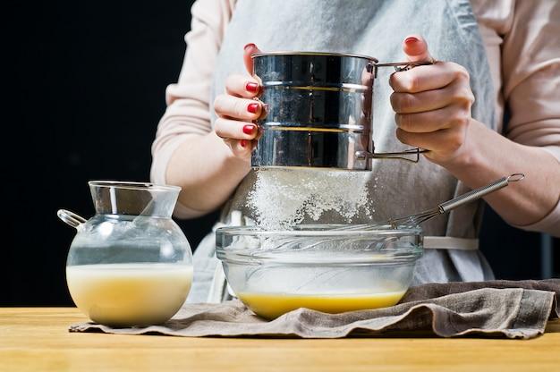 O chef peneira a farinha em uma tigela.