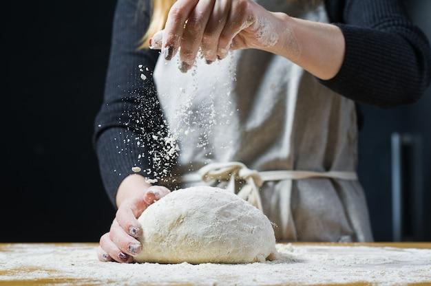 O chef polvilha farinha sobre a massa de fermento em uma mesa de madeira.