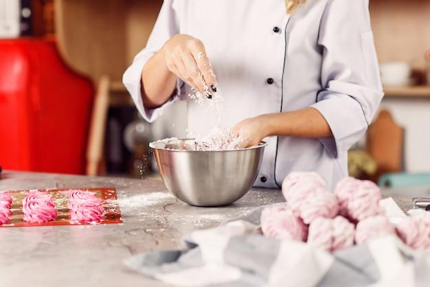 O chef polvilha marshmallows caseiros com açúcar em pó. o conceito de cozinha caseira. processo de preparação de marshmallow.