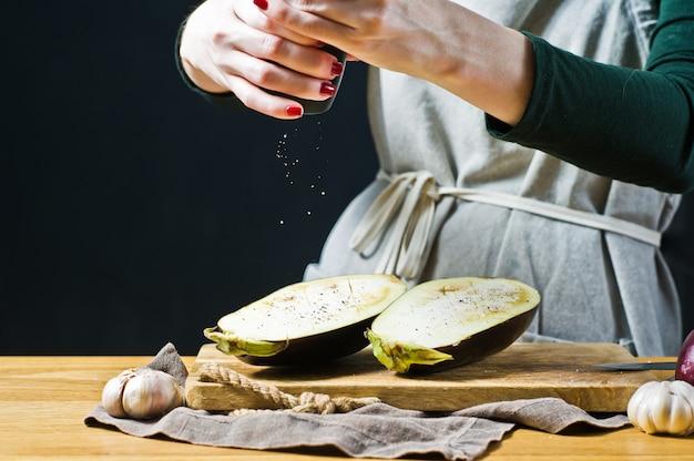 O chef polvilha sal na berinjela grelhada vista lateral, espaço para texto
