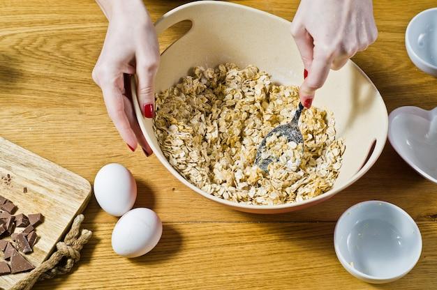O chef prepara biscoitos de aveia, mistura ingredientes: flocos de aveia, manteiga, açúcar, ovos, chocolate.