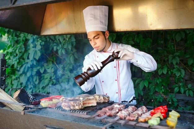 O chef prepara carne no churrasco.