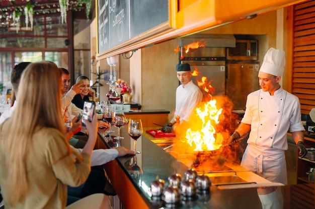 O chef prepara comida em frente aos visitantes no restaurante