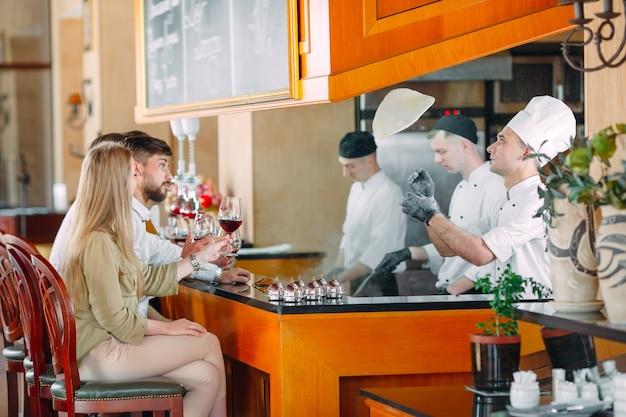 O chef prepara comida na frente dos visitantes no restaurante
