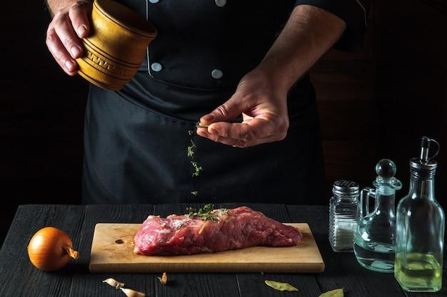 O chef prepara filés de carne bovina crua e adiciona temperos secos para a marinada ambiente de trabalho