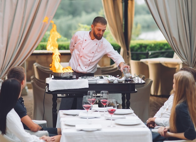 O chef prepara o foie gras diante dos convidados.
