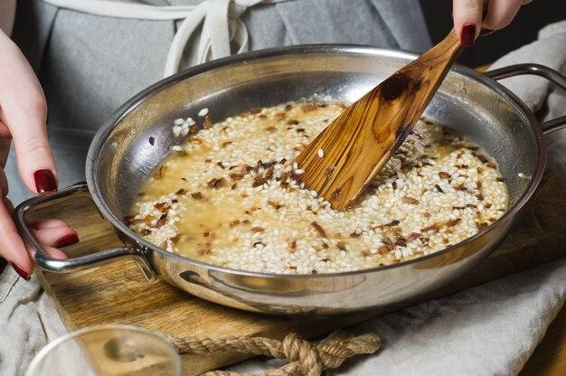 O chef prepara o risoto italiano. camarão, vinho branco, arroz, cebola, tomilho, alho.