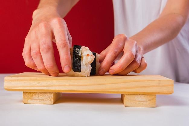 O chef prepara o tradicional sushi com camarão, arroz e algas em uma placa de madeira.
