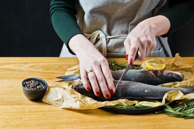 O chef prepara robalo em uma mesa de madeira.