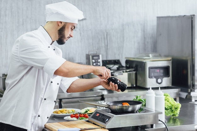 O chef prepara salmão fresco, polvilhando sal com os ingredientes. gelo congelando no ar preparando para cozinhar comida de peixe
