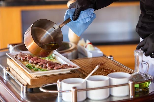 O chef prepara um bife no salão do restaurante