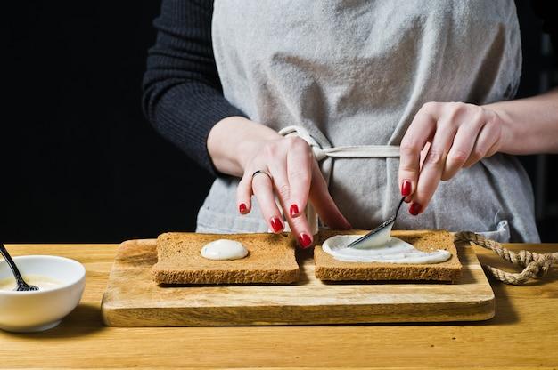 O chef prepara um sanduíche de pão preto, esfrega o molho na torrada.
