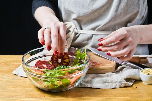 O chef prepara uma salada com laranjas vermelhas e rúcula.