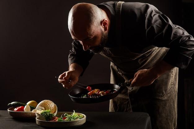 O chef prepara uma salada de frutos do mar e vegetais