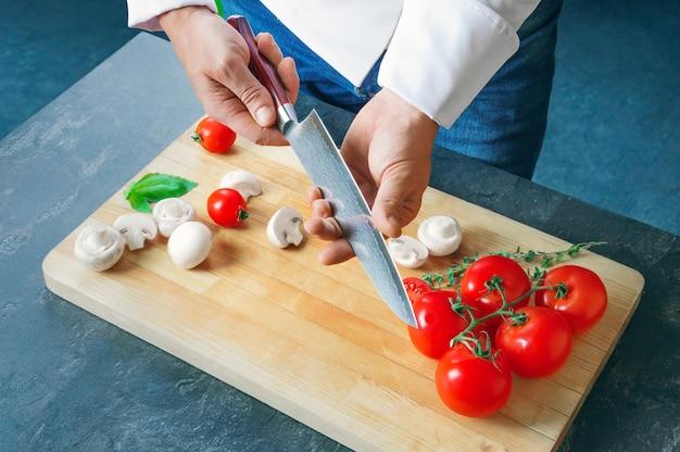 O chef profissional corta vegetais com uma faca afiada de aço damasco. mídia mista