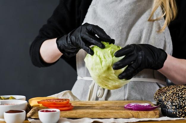 O chef puxa a alface. o conceito de cozinhar um hambúrguer preto. receita de hambúrguer caseiro.