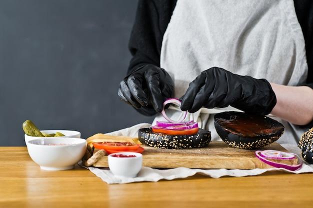 O chef recolhe os ingredientes de um cheeseburger. o conceito de cozinhar um hambúrguer preto. receita de hambúrguer caseiro.