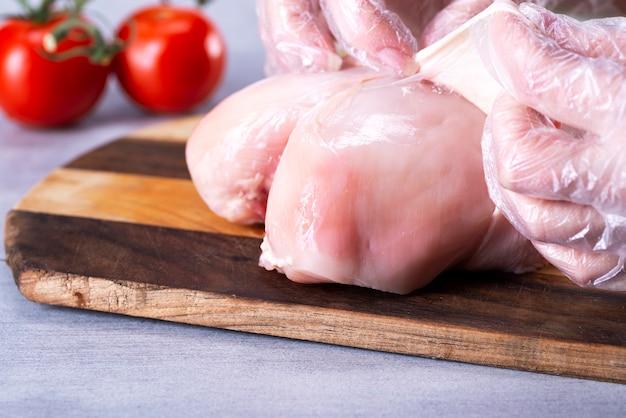 O chef remove a pele do peito de frango para reduzir a quantidade de gordura na comida