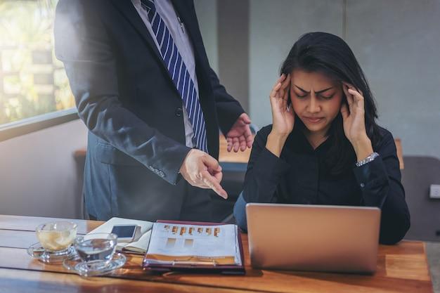 O chefe culpou a secretária pelo trabalho e teve uma dor de cabeça no consultório.