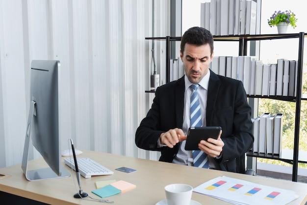 O chefe da empresa está estressado com os negócios enquanto conversa no tablet do computador.