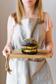 O chefe está segurando uma tábua de madeira com um hambúrguer preto.