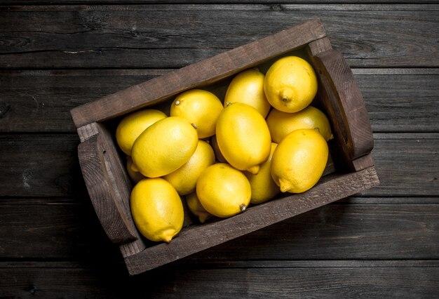 O cheiro de limão fresco em caixa de madeira. na mesa de madeira preta