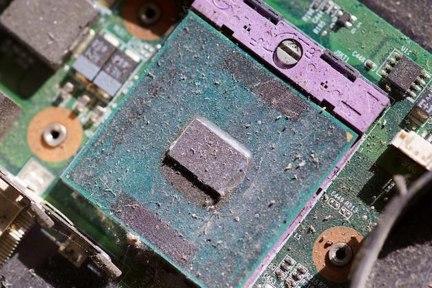 O chipset eletrônico do processador do computador de close-up na placa-mãe está coberto de poeira